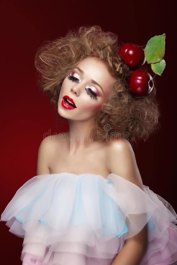 Woman with artistic make-up and cherry. royalty free stock image