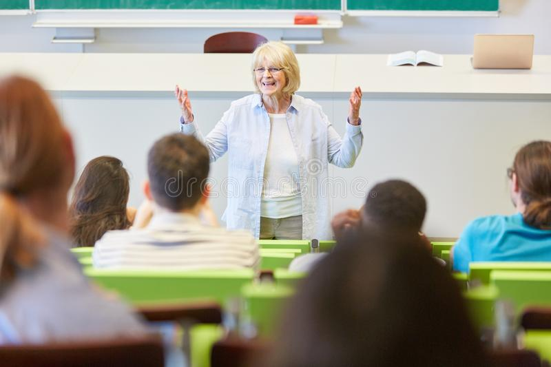 Woman as lecturer teaches students class stock photos