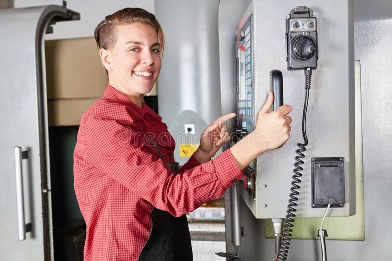 Woman as machinist works with CNC machine stock photos