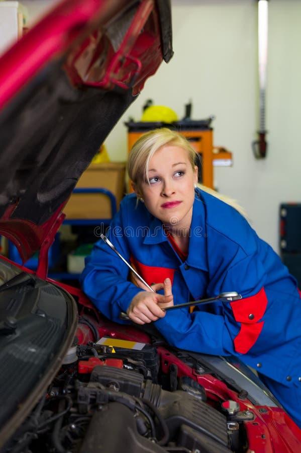 Woman as a mechanic in car workshop