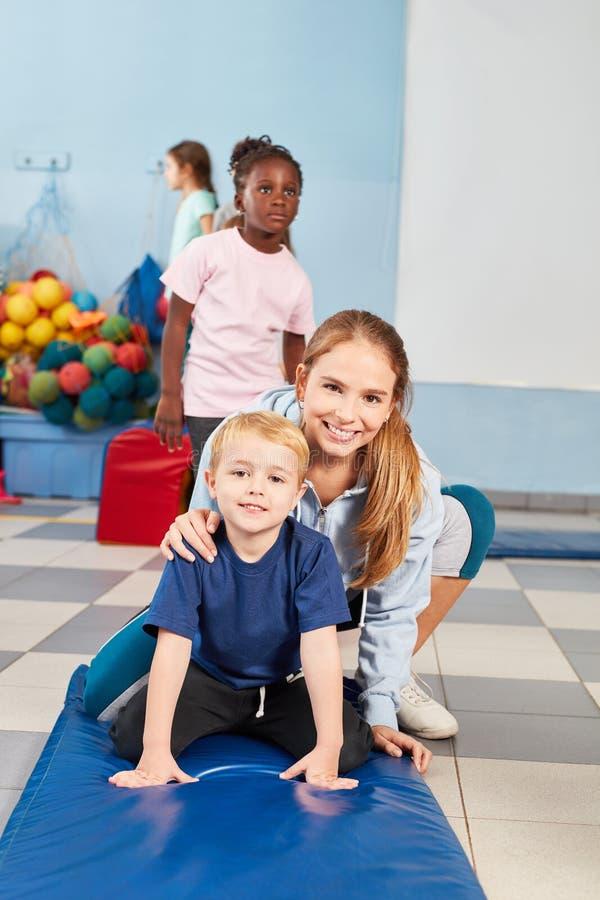 Woman as a sports teacher and a boy stock photo