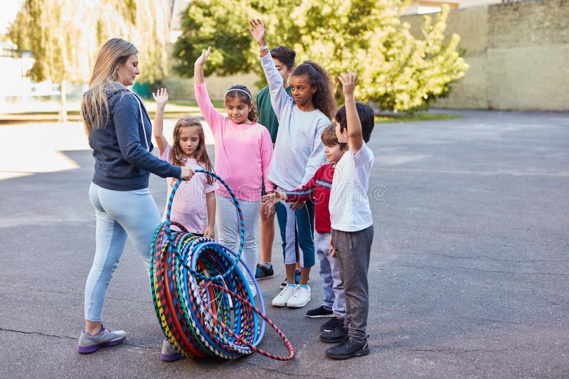 Woman as a teacher distributes hoops to children. Woman as teacher distributes hoops in physical education to children at summer camp stock images