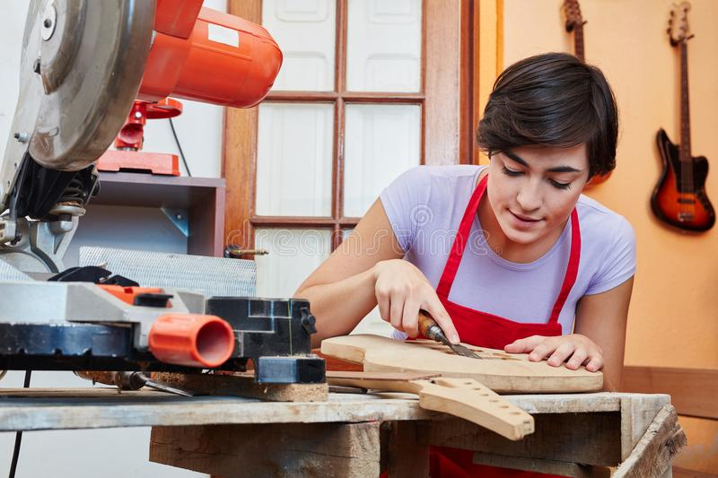 Woman as trainee learns guitar making art. In luthier workshop royalty free stock image