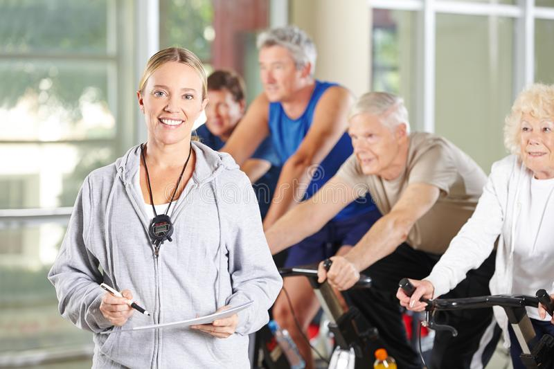 Woman as a trainer for seniors in the fitness center stock photography