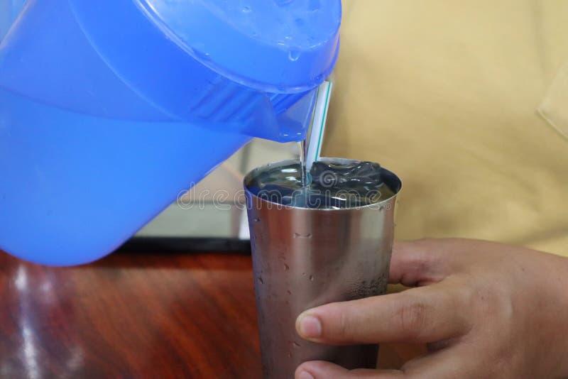 Woman& asiatico x27; la mano di s sta versando l'acqua nel vetro immagine stock libera da diritti