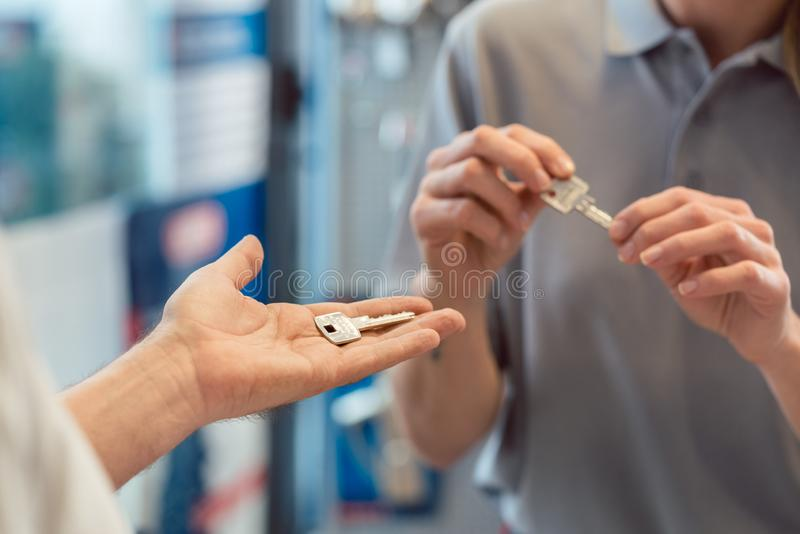 Woman asking locksmith to make a key copy. Duplicate, close-up royalty free stock image