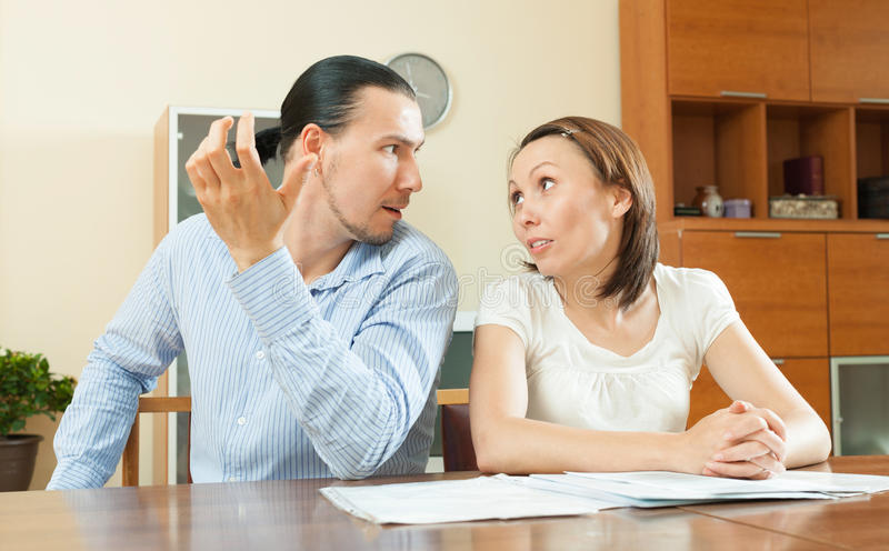 Woman asking for money from husband for the purchase. Adult men and women having quarrel about documents at home royalty free stock image