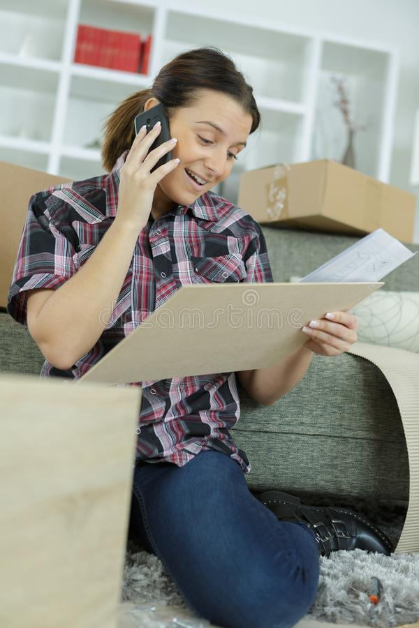 Woman assembles furniture while asking for help royalty free stock image