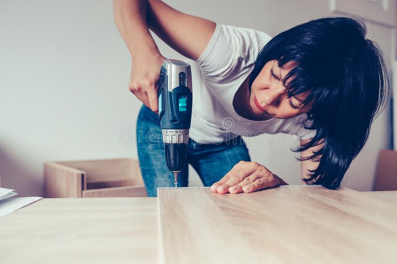Woman assembling furniture in her home, using a cordless drill stock photos