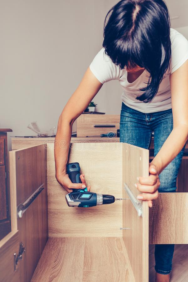 Woman assembling furniture and holding a cordless drill royalty free stock photography