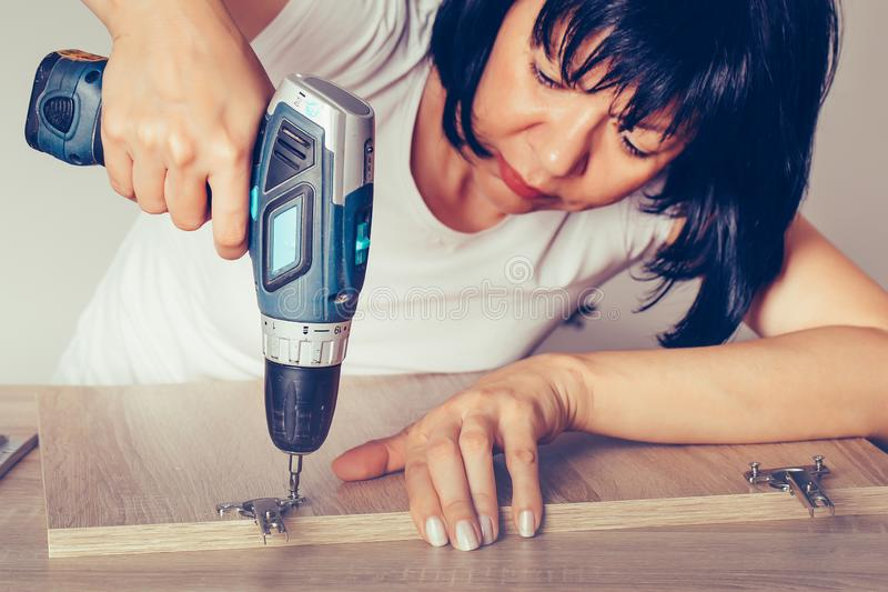 Woman assembling furniture in her home and using a cordless drill stock photo