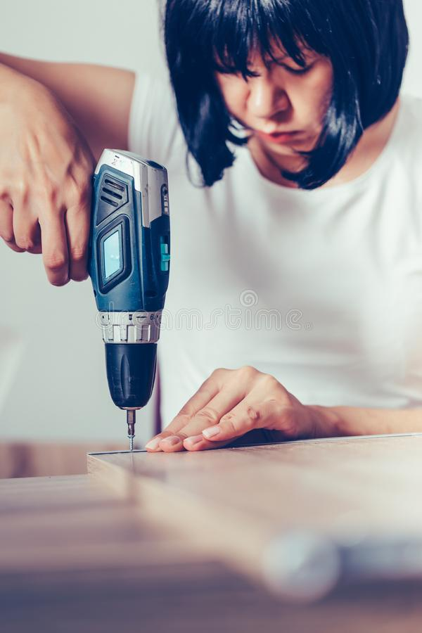 Woman assembling new furniture in her home and using a cordless drill royalty free stock photo