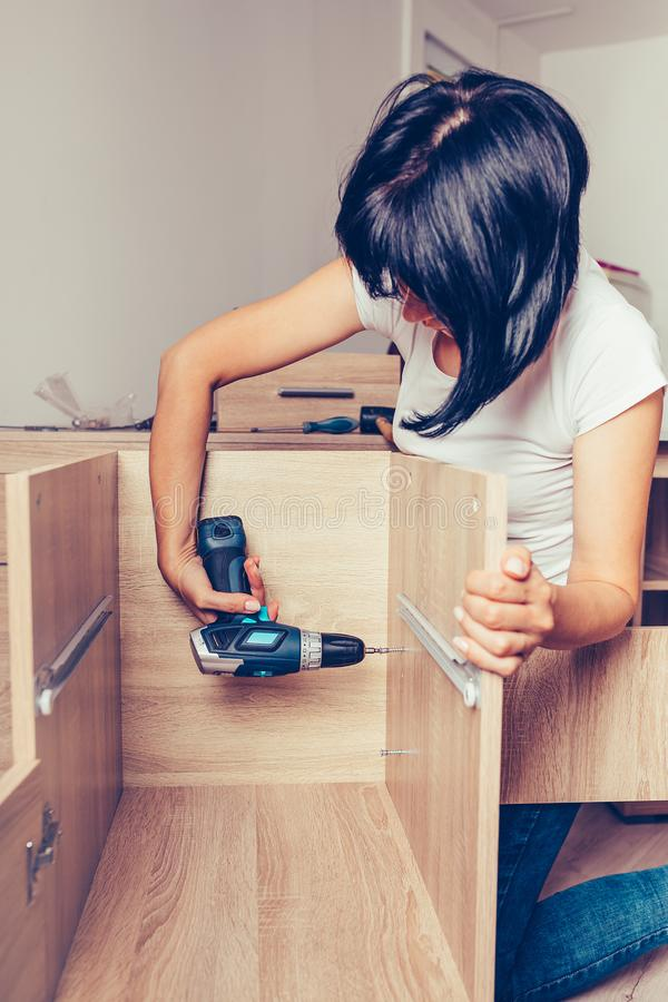Woman assembling new furniture in her home using a cordless drill stock image