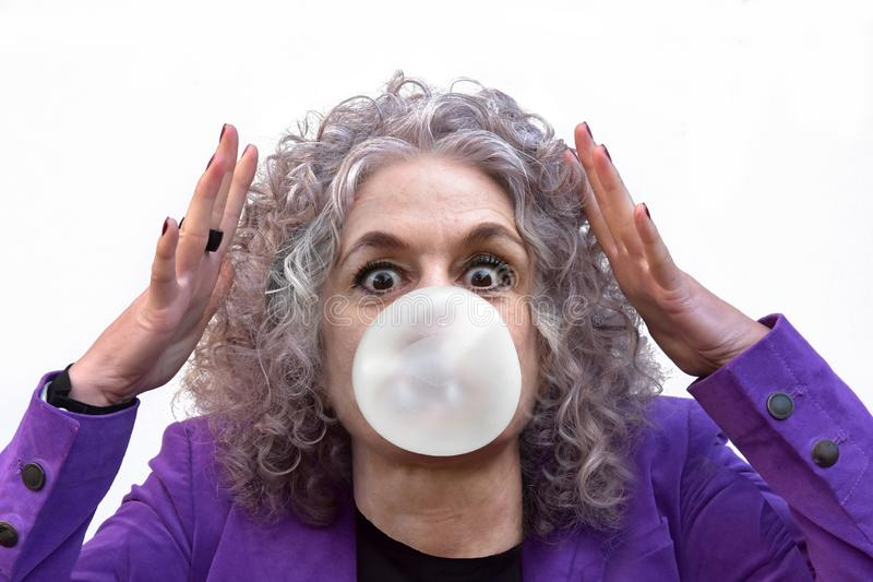 Woman is astonished she has managed to make a thick bubble gum. Woman with curly hair is surprised. She has managed it to make a thick bubble gum royalty free stock images