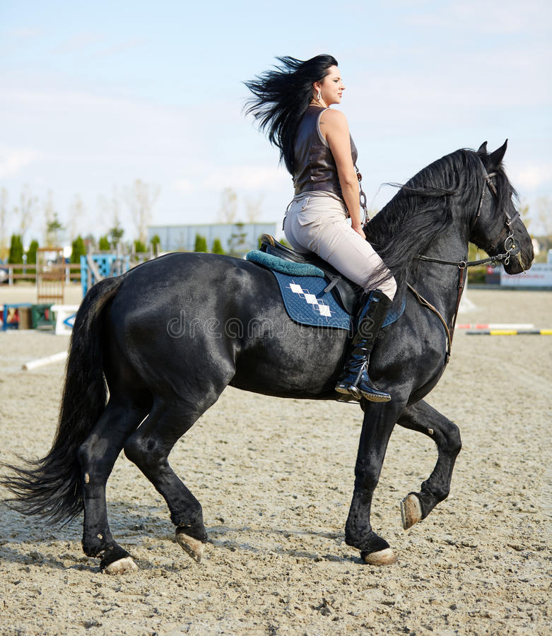 Woman astride a horse stock image