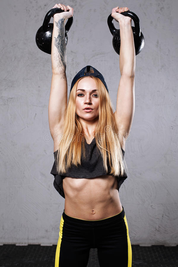 Woman athlete doing military press. With two kettlebells royalty free stock photo