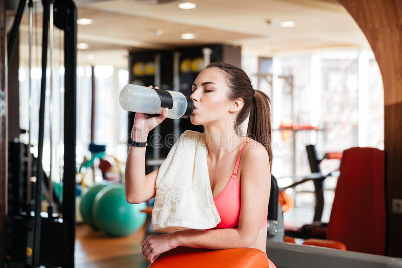 Woman athlete drinking water on training in gym stock images