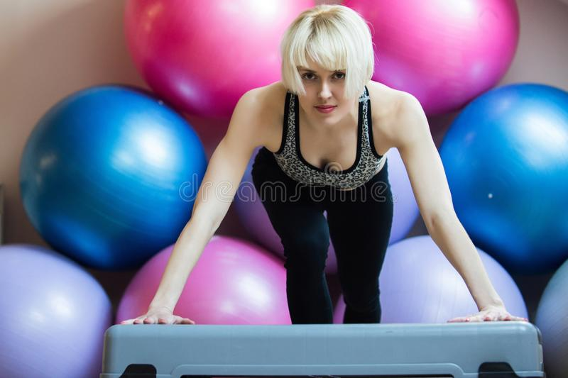 Woman athlete keep arms straight on stepper in gym. With colorful fit balls. Endurance, strength and fitness concept. Sport, health, activity stock images