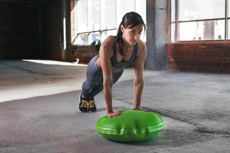 Woman athlete push ups on a gymnastic ball. Fitness concept stock photography