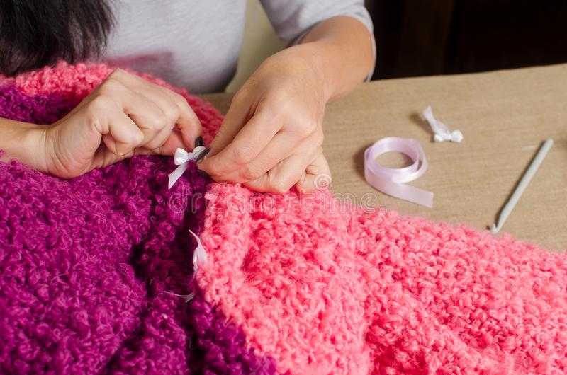 a woman attaches a white bow to a knitted by hand lilac-pink plaid stock images
