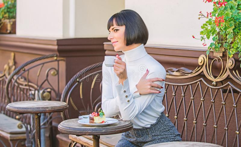 Woman attractive elegant brunette eat gourmet cake cafe terrace background. Pleasant time and relaxation. Delicious. Gourmet cake. Girl relax cafe with cake royalty free stock photo