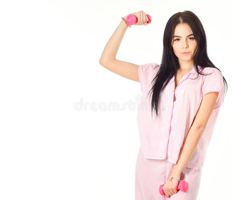 Woman, attractive young lady in pajama. Morning exercises concept. Girl on smiling face holds dumbbells, enjoy morning royalty free stock photo