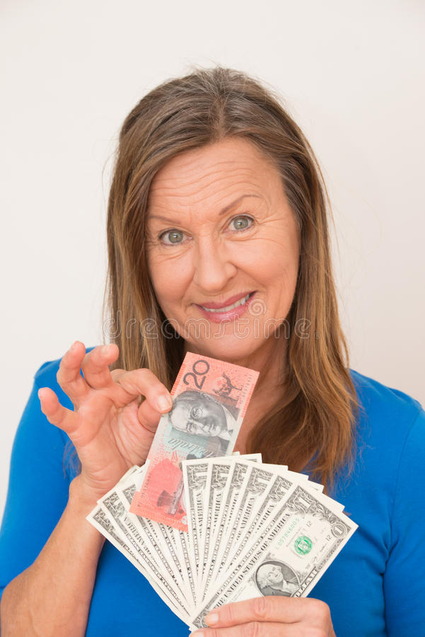 Woman australian and american dollar notes. Portrait attractive mature woman presenting relaxed smiling Australian and US dollar notes, isolated, bright royalty free stock photos
