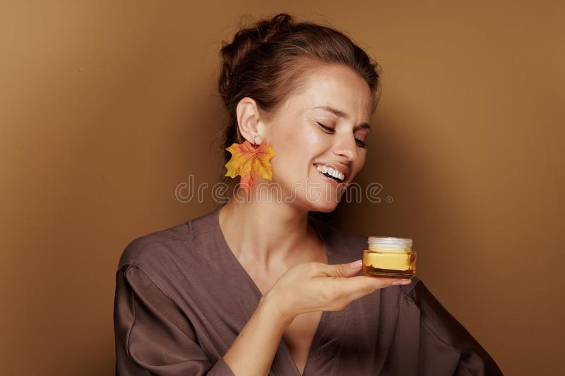 Woman with autumn leaf earring enjoy fragrance of facial creme royalty free stock image