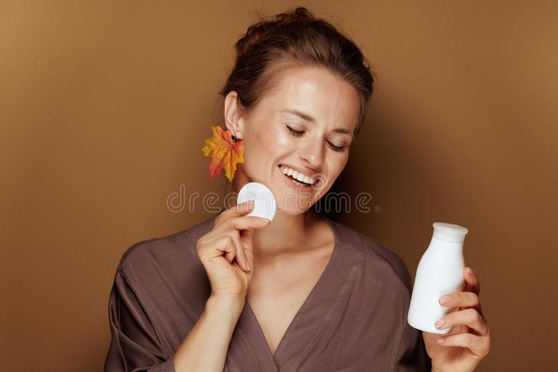 Woman with autumn leaf earring using face cleansing milk stock photos