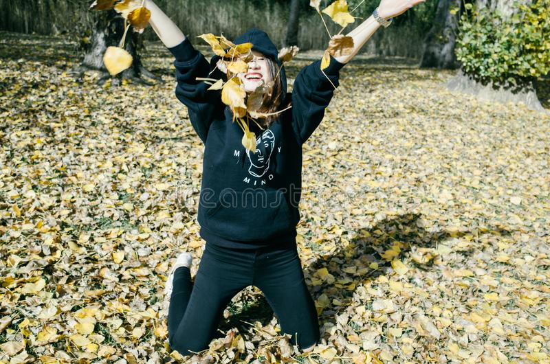 Woman with autumn leaves in hand and fall yellow maple gar royalty free stock image
