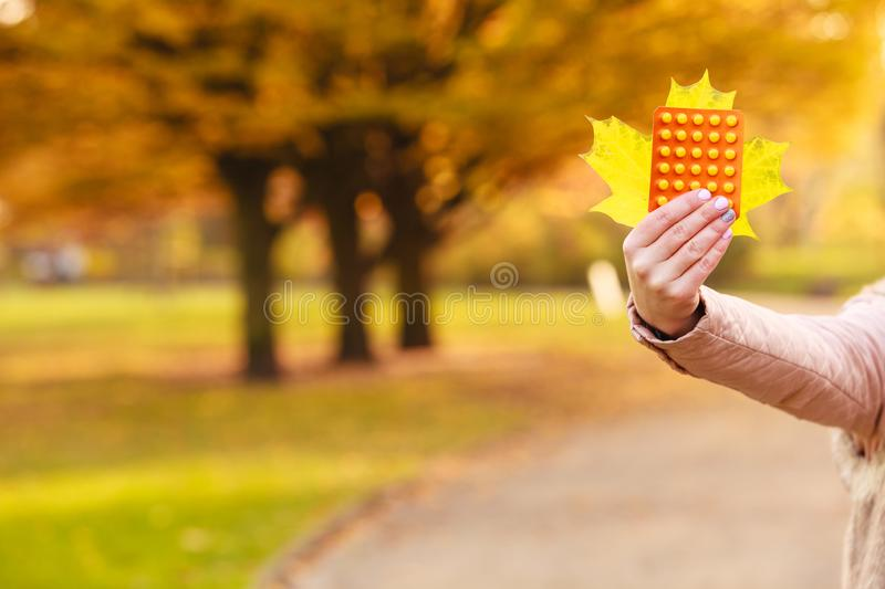 Woman in autumn park holding vitamins medicines. Showing how to deal with seasonal autumnal fever and supporting immunity during cold days stock image