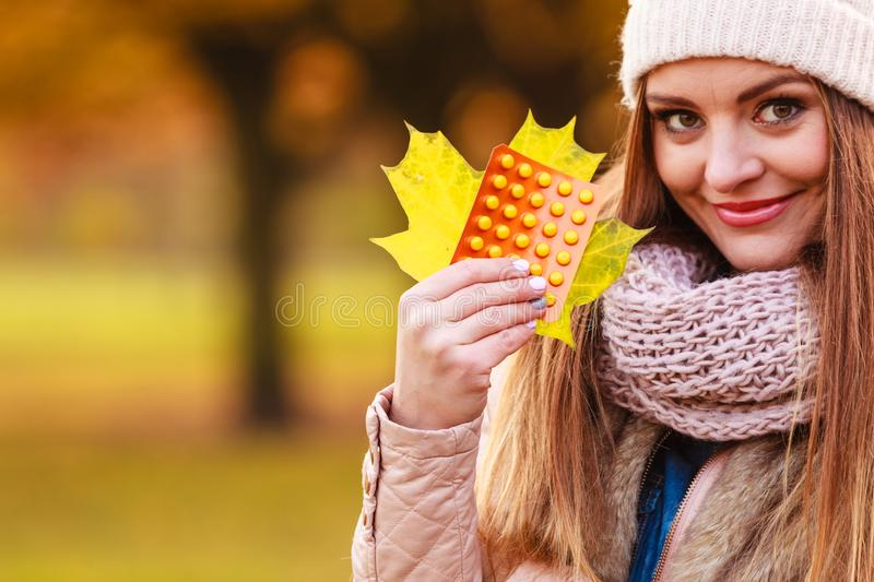 Woman in autumn park holding vitamins medicines. Showing how to deal with seasonal autumnal fever and supporting immunity during cold days royalty free stock images