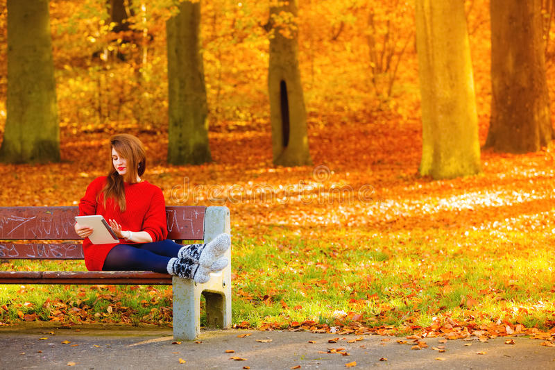 Woman in autumn park using tablet computer reading. stock photos