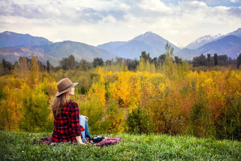 Woman at autumn picnic. Woman in red checked shirt and hat sitting on the grass with photo camera at autumn forest and mountains background stock image