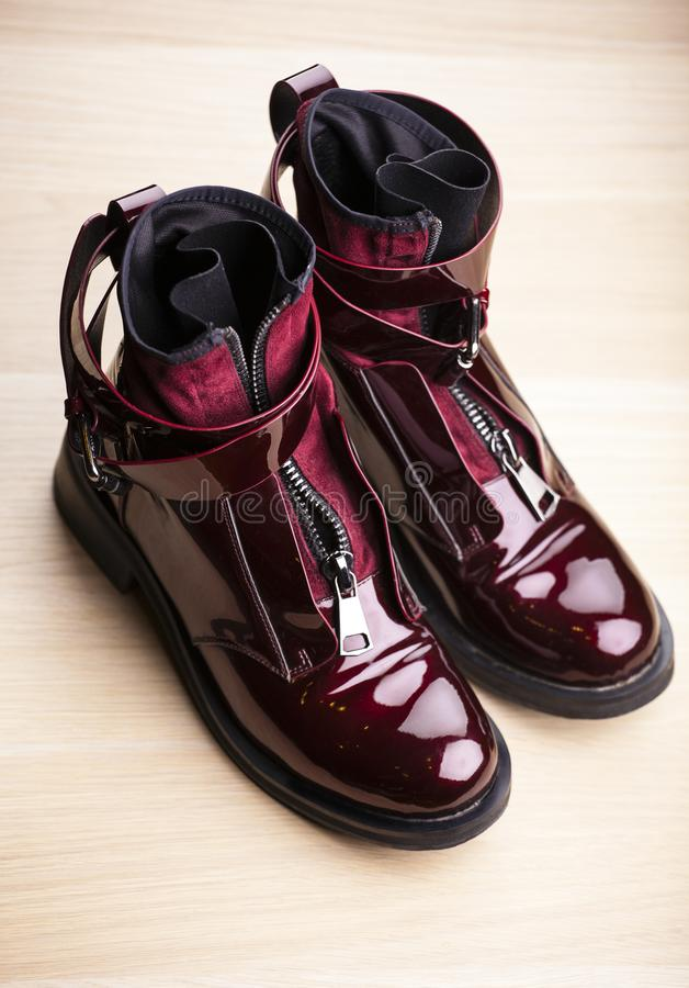 Woman autumn season red varnished boots wooden table stock photography