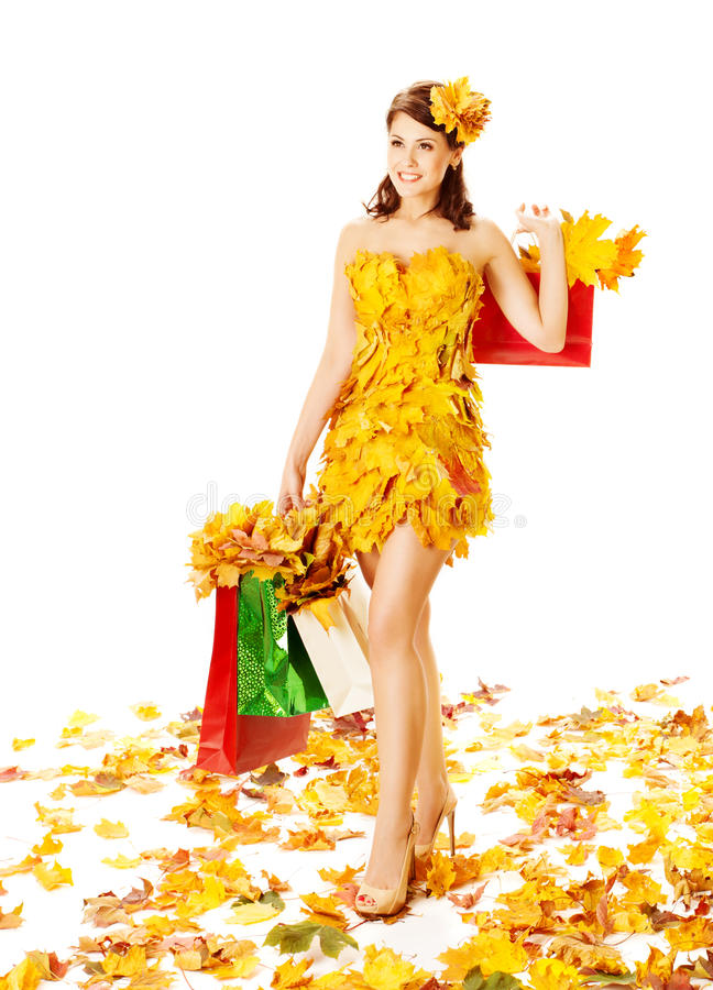 Woman autumn shopping in dress of maple leaves over white. Autumn woman with shopping bags in dress of maple leaves. White background royalty free stock photo