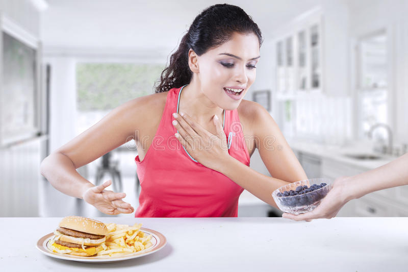 Woman avoids hamburger and choose fresh blueberry. Healthy Indian woman avoids unhealthy hamburger and choose a bowl of fresh blueberry in the kitchen stock photo