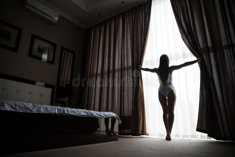 Woman is awoke and standing before window. Girl is opening curtains and meeting sunrise stock photography