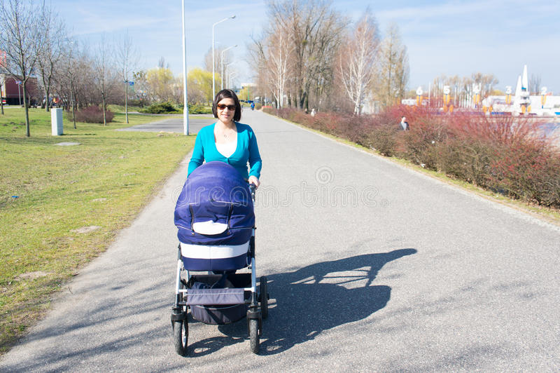 Woman with baby buggy. Woman walking with her baby buggy at a park stock image