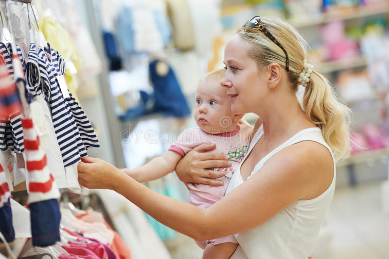 Woman with baby in shop stock photos