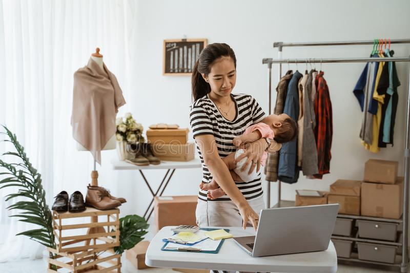 Woman with baby working from home of her online ecommerce shop. Portrait of women with baby working from home of her online ecommerce shop royalty free stock images