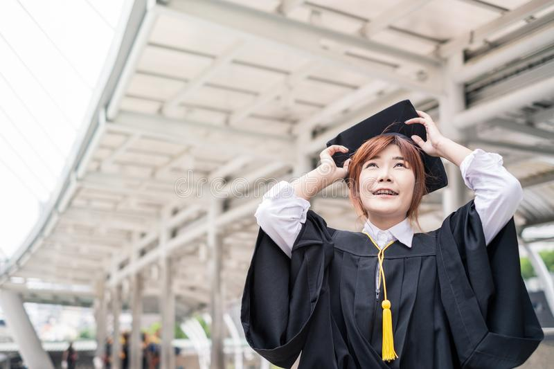 Woman bachelor`s degree wearing graduate dress with holding hat royalty free stock photo