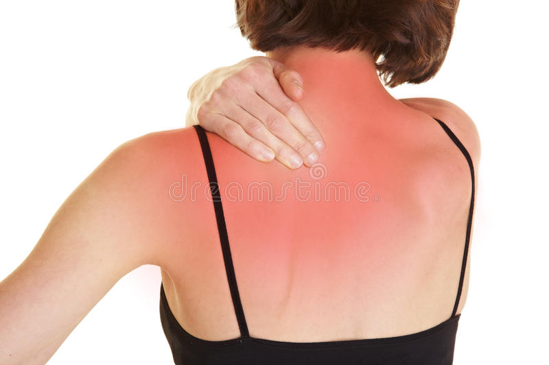 Woman with back pain. Young woman massaging her red aching back stock photo