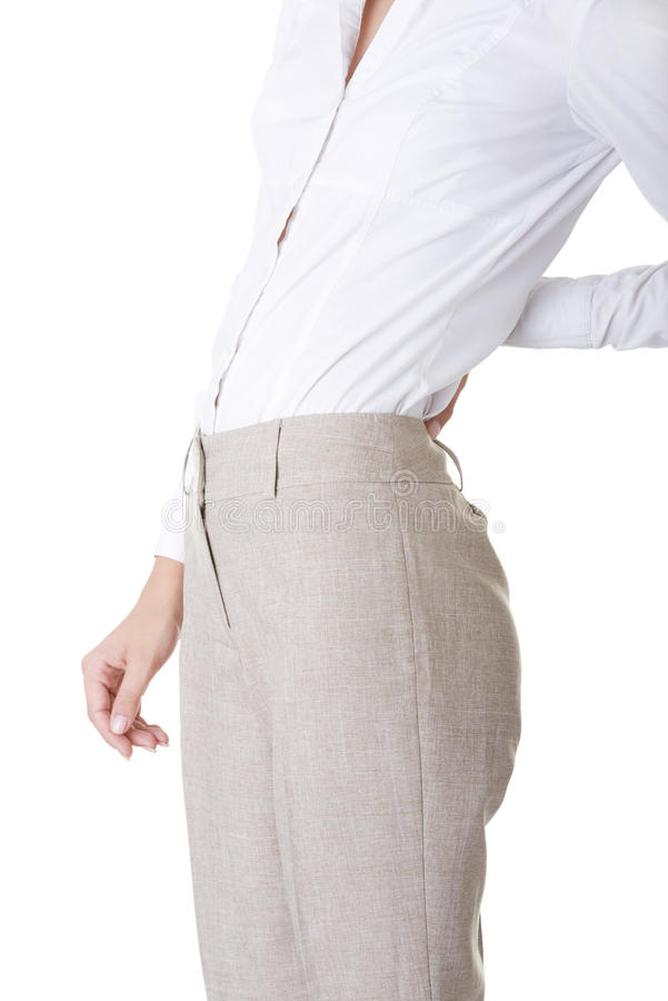 Woman with back pain. Holding her aching hip stock photos