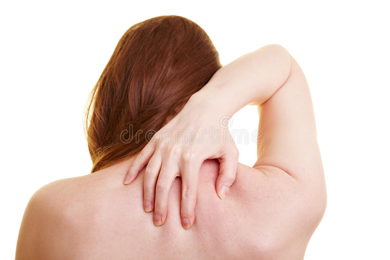 Woman with back pain from behind. Woman from behing touching her aching back stock photography