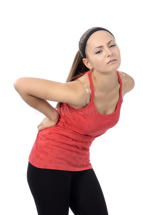 Woman Back Pain. Woman bends over and flinches in pain in her back. fitness concept stock photography