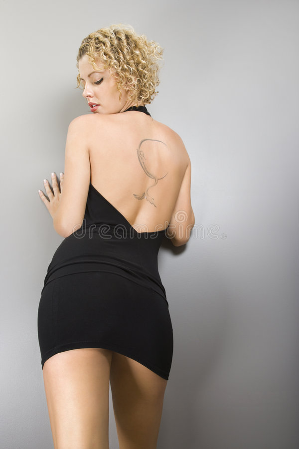 Woman with back tattoo. Back view of Caucasian young adult woman leaning on wall with tattoo stock photography