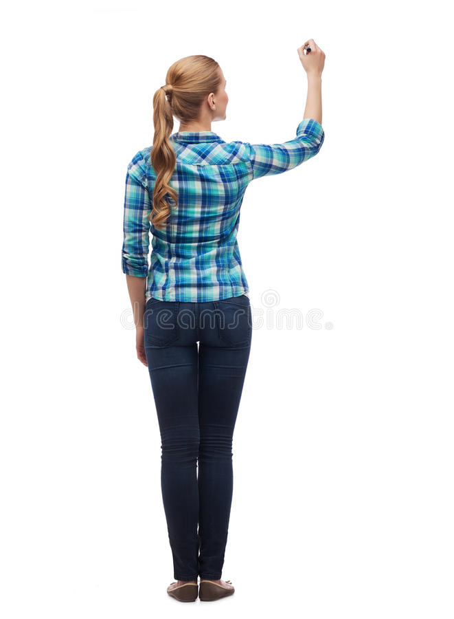Woman from the back writing something in the air. Education and advertising concept - young woman from the back writing something in the air stock images