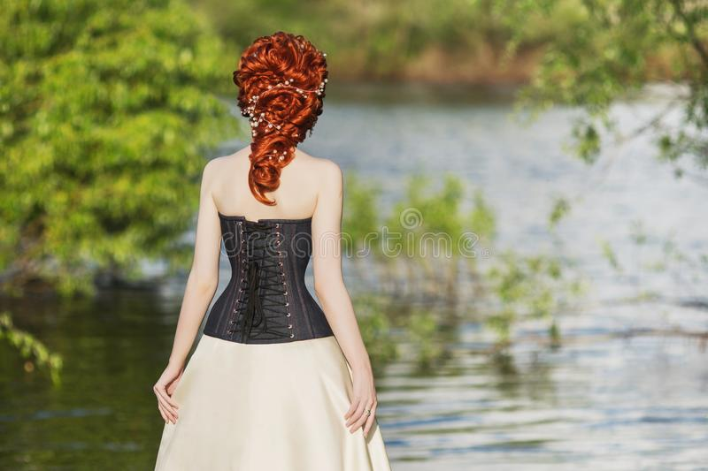 Woman back. Young victorian princess with hairstyle on nature background. Model in corset. Rococo queen in white historic dress. Against backdrop of blue water royalty free stock photo
