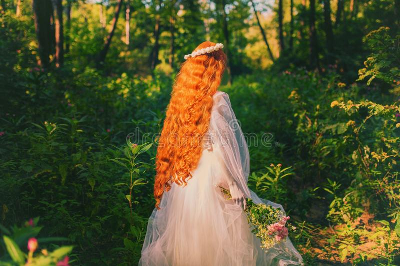 Woman back. Young victorian princess with long hair on nature. Model in veil with bouquet of flowers. Princess in white dress. Against backdrop of nature stock photo